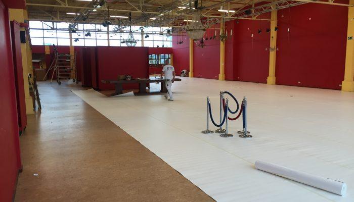Afplakken van de vloeren met stucloper, alvorens te kunnen starten met het spuiten van de wanden.